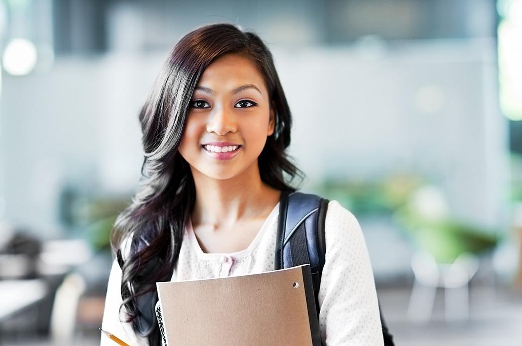 Una adolescente sonriente usando una mochila y llevando sus cuadernos