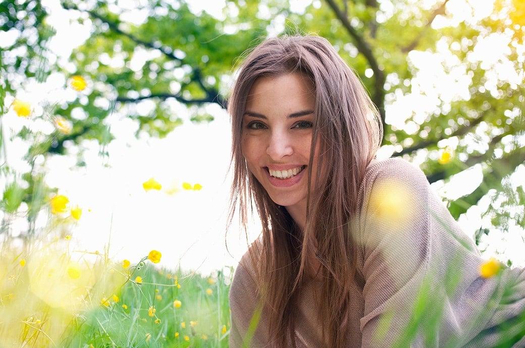 Mujer adulta sonriendo mientras descanza en la grama con el sol brillando