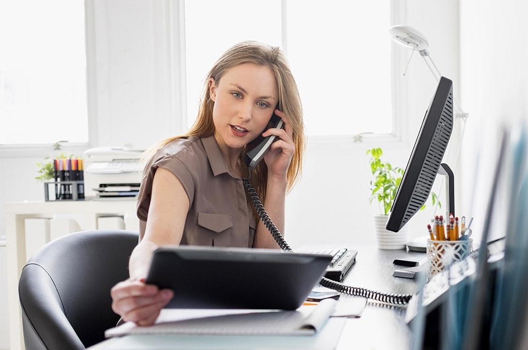 Una mujer en su escritorio en la oficina mirando una tableta mientras habla por teléfono