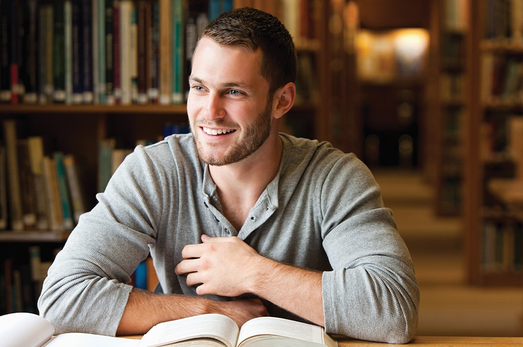 Un hombre en la biblioteca sonriendo con libros sobre la mesa