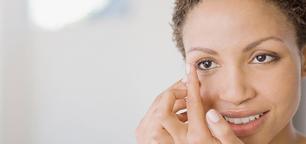Una mujer con una lente de contacto en su dedo a punto de ponerlo en su ojo