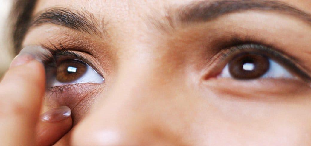 """""""Close up"""" de una mujer joven mirándose en el espejo mientras se coloca sus lentes de contacto"""